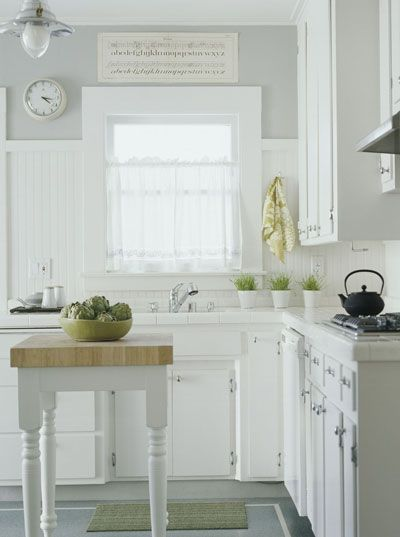 Light, bright and tiny kitchen. The white and very light grey keep things airy and uniform. The little island is cute, but I question how functional it might be.