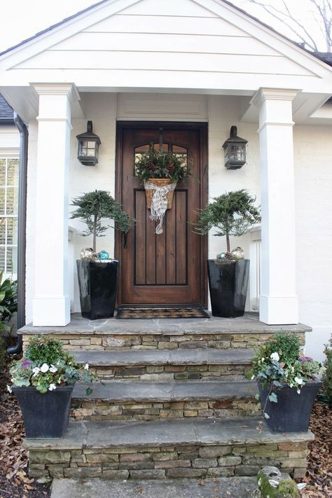 white home with a wooden front door and stone accents