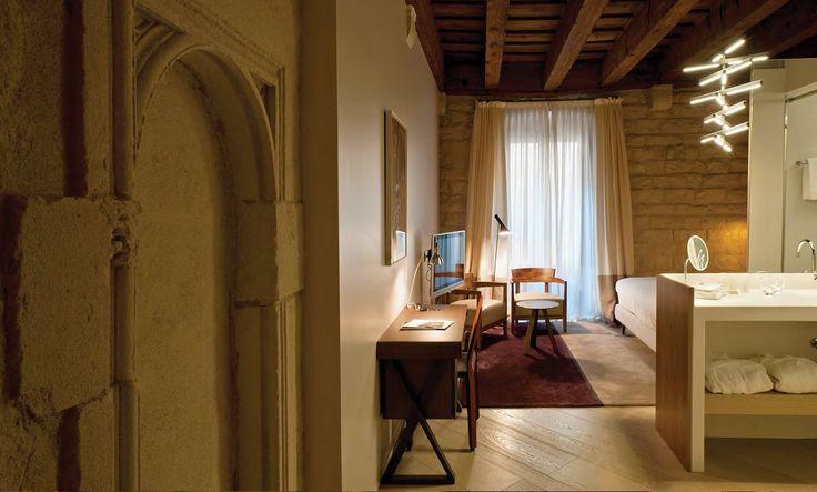 la luz que entra por las antiguas ventanas abocinadas contrasta con las fuentes de iluminación contemporáneas. Ambas crean un efecto que resalta las texturas y colores de los muros.