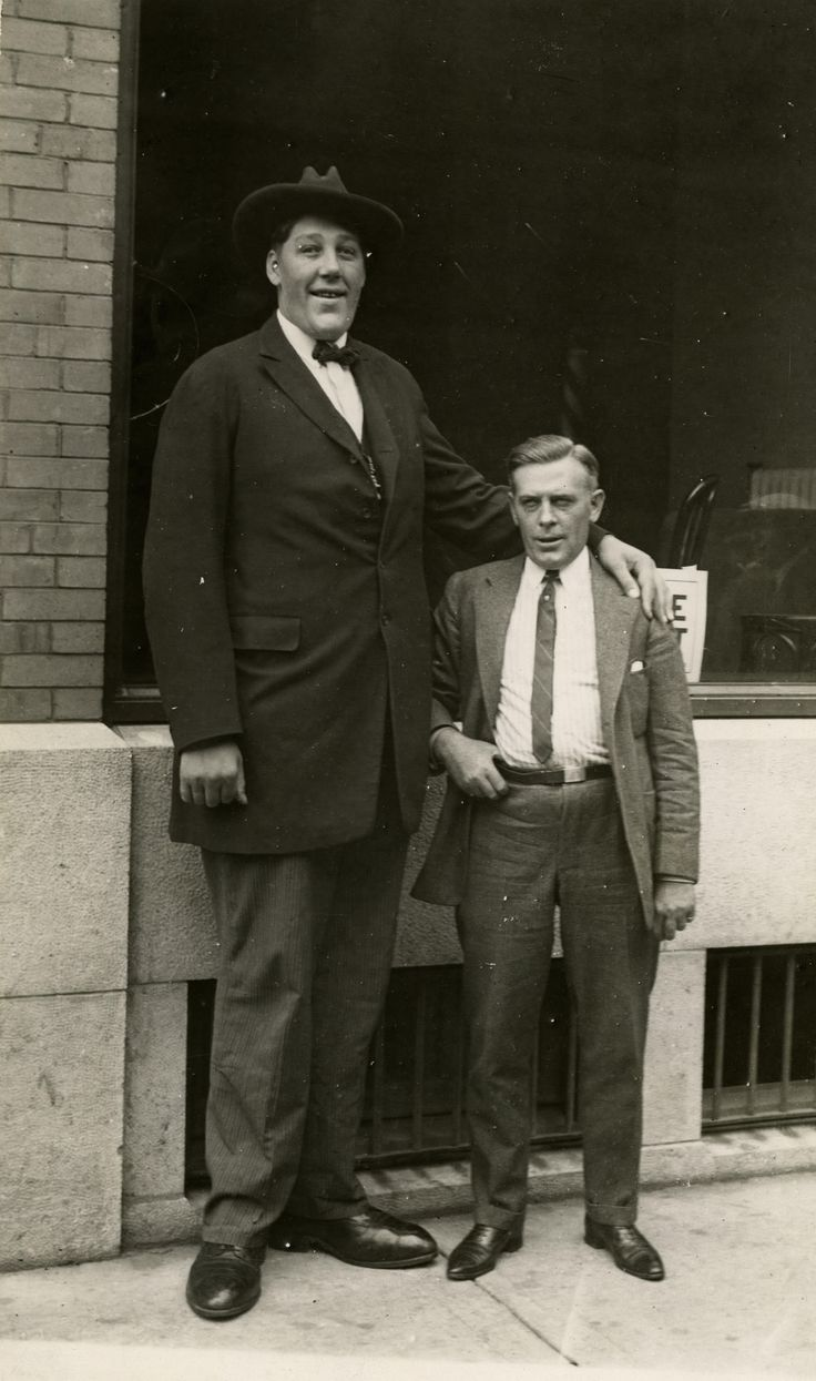 """From the Globe (August 26, 1922): """"John Aasen, Holland's giant, 8 feet 9 inches high, who arrived yesterday for the Canadian National Exhibition. Beside him is Mr. L.H. Muldoon, Manager of the King Edward Hotel, himself nearly six feet tall."""". From the Toronto Public Library's Digital Archive."""