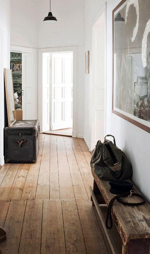 czarny kufer kolonialny,drewniana wiejska ławka,drewniane deski na podłodze  i duża czarno-biała fotografia na białej ścianie w przedpokoju