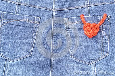 Heart-shaped knot on texture of blue jeans