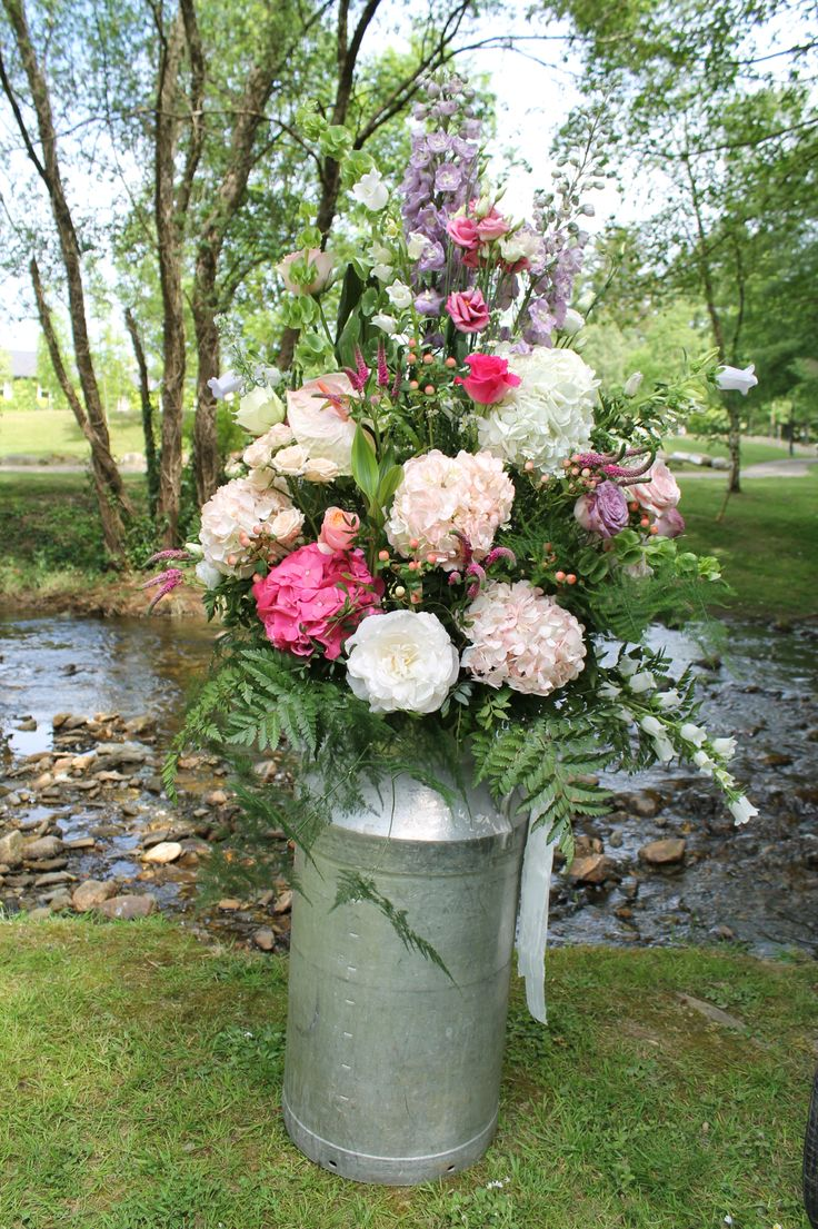 Large floral arrangement in milk churn