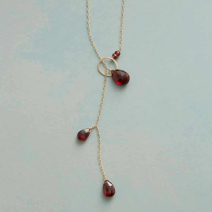 """AVANT-GARNET NECKLACE--Garnet briolettes slip through a golden hoop, making an out-of-the-ordinary clasp the center of attention on our necklace. Kyoko Honda's avant-garde design is handmade in USA of 14kt gold. 18""""L."""