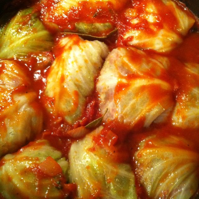 Paleo Stuffed Cabbage Rolls - One large head of cabbage ( You'll need to get about 12 leaves to use), 1 lb ground beef, 1 lb ground pork, 1 small cauliflower (riced) or half a large head, half of a sweet onion, 4-6 large cloves of garlic, 2-3 tbs olive oil, 1 can tomato paste, 2 cans of crushed tomatoes, 2 tbs white wine or red wine vinegar, 2 -3 tbs oregano, 2 eggs, salt and pepper to taste