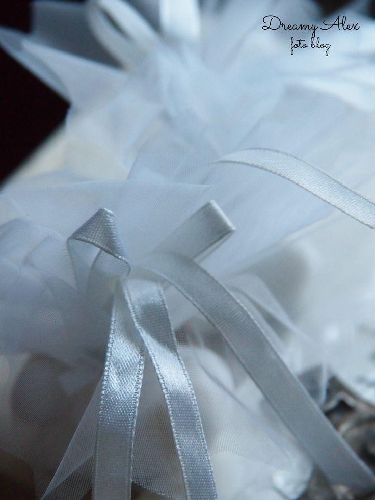 Białe, tiulowe sakiewki z cukierkami - pamiątka z wesela bliskich osób.