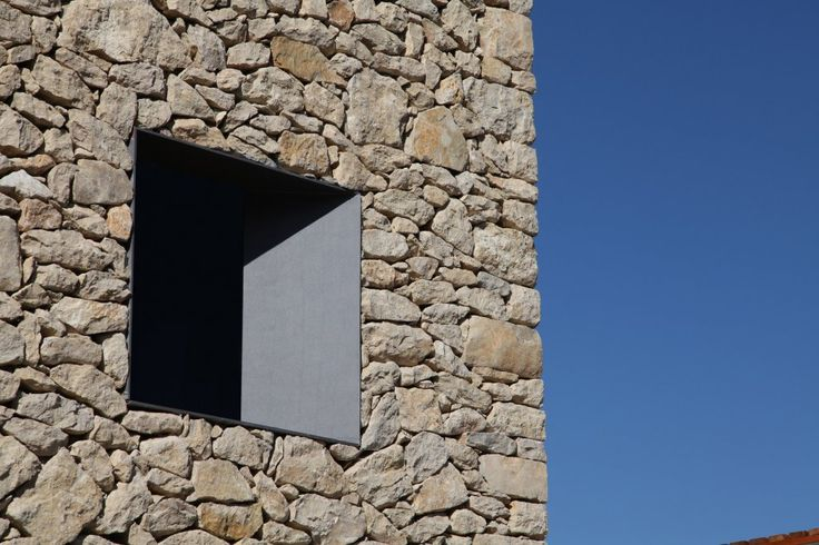 Clean window reveal inside a stone wall. Refugo en La Vall de Laguar by Ernproyecto Arquitectura.