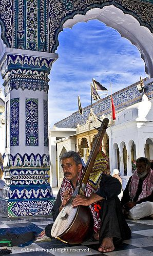 """Musician/devotee playing """"TAMBOORA"""" from dawn to dusk and sing Sufi / Folk songs & chants at the shrine to show respect 