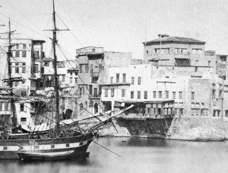 Χανιά.  Τοπανάς. Η αρχή της οδού Αγγέλου. Ανάμεσά τους ένα πολεμικό ιστιοφόρο (μπρίκι). Λεπτομέρειες που δεν υπάρχουν στις λήψεις απ' το 1890 και μετά:  Το διαβατικό (αψίδα) στο ξεκίνημα της οδού Αγγέλου, το μεγάλη ξύλινο σαχνισί μπροστά στο σημερινό Ναυτικό Μουσείο και η  θάλασσα που εισχωρεί από κάτω  (βενετσιάνικη ιχθυοπαγίδα;). Φωτογραφικό Αρχείο Μανώλη Μανούσακα από την έκθεση: ´ΧΑΝΙΑ-ΒΕΝΕΤΙΑ χθες και σήμερα´