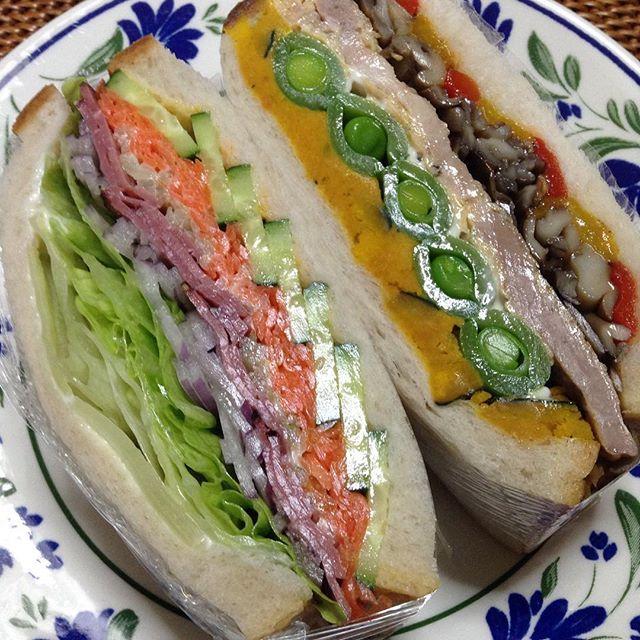 今日のサンドイッチ 左は、レタス・アーリーレッド(紫タマネギ)・パストラミ・セロリのサラダ・キャロットラペ・キュウリ・マスタード 右は、ハニーマスタード・ローストカボチャのサラダ・スナップエンドウ・ポークピカタ・舞茸のガーリックバターソテー・赤&黄色のパプリカローストマリネ 肉・肉だけど野菜もたっぷり💕 たくさん食べて頑張ろう👍#サンドイッチ #モリモリ #肉#野菜たっぷり