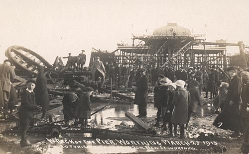 DescriptionWreckage of Worthing Pier after it was destroyed in a storm in the night of 22-23 March 1913. Men women and children stand on beach at low tide looking at twisted girders and other wreckage. Undamaged part of the pier with Sputh Pavilion still standing in background. People on beach wearing winter coats and hats.