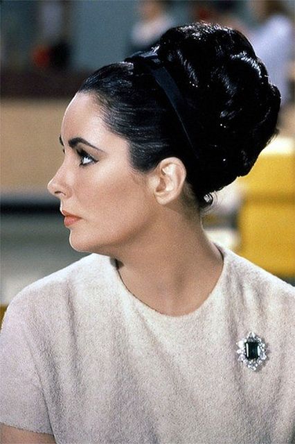 Elizabeth Taylor in The V.I.P.s (1963).  Please note the Bulgari brooch Richard Burton gave her, mounted with a twenty-carat emerald.