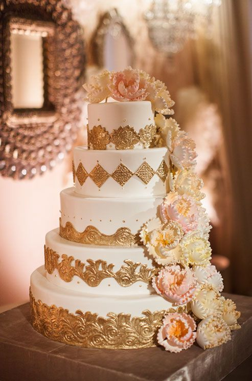 How stunning is this gilded five tier wedding cake adorned with cascading pink blooms?