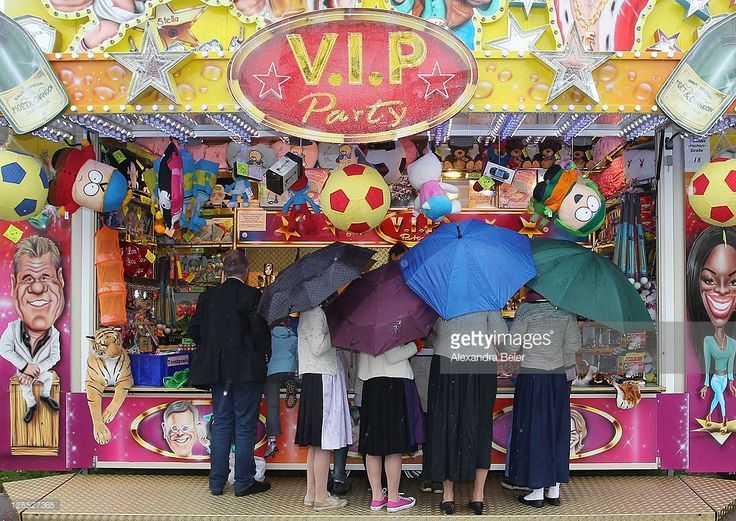 Visitors hold umbrellas as they stand at a fairground booth during day 2 of the Oktoberfest 2011 beer festival at Theresienwiese on September 18, 2011 in Munich, Germany.