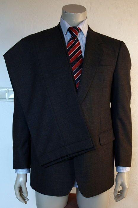 Burberry - 2-delig kostuum  2-delig kostuum van Burberry 's model Lyon U: maat 25 = 50/M (NL/DE) stof: 100 % zuiver scheerwol voering: 100 % viscose grijs gemêleerd-Colbertjas met 2 x knoopsluiting 3 x zakken; 2 x met overslagklep (1 x met extra binnenzakje) 3 kissing buttons op mouw en enkele achter split (25 cm) 3 x binnenzakken van 13 cm breed (1 x verdeeld in 8 cm en 5 cm) en 1 x zakje van 11 cm breed glanzend zwarte binnenstof met legio maal geborduurd Burberry 's logo inclusief…