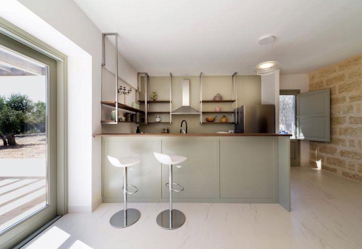 Cucina moderna su disegno Iosa Ghini, sgabelli Leo, design Iosa Ghini per Brf. La zona giorno della masseria salentina è rivolta verso Sud e illuminata da ampie vetrate