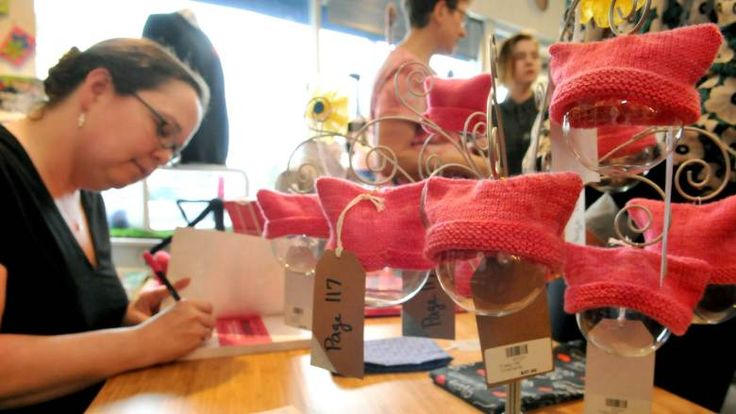 Local author and craftivist, Lara Neel, has helped spawn a movement of craftivisim or the making of crafts that protest something. Neel was at Knit and Bolt in NE Minneapolis signing copies of her new book, 'Crafting the Resistance', on Friday, August 25, 2017. Hanging to her right are some one-of-a-kind glass balls adorned with pussy hats that she knitted and are included in her book.  (Ginger Pinson / Pioneer Press)