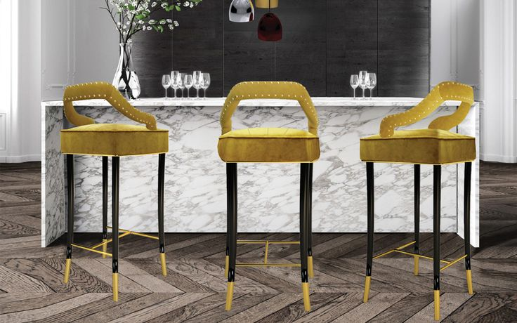 Kelly bar chair dazzles in its smooth mustard velvet and long, elegant legs. The glossy black structure finished with a delicate touch of golden leaf complements the golden tacks adorning the contours of the gracious backrest.