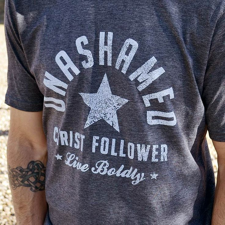 "This men's Christian t-shirt is ultra-soft and graphically bold. A Christian shirt for men that reads ""Unashamed Christ Follower"" in a sporty, distressed design. The print is off-white on a charcoal poly-cotton gray t-shirt - Inspired by 2 Timothy 1:8"