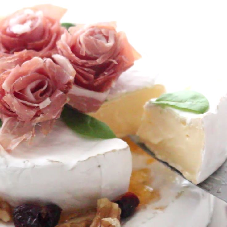"This ""cake"" is actually two rounds of brie that are decorated with prosciutto roses! If you're looking for a way to dress up a traditional cheese board and add a cute twist to a party, this would be perfect!"