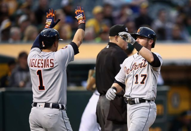 Andrew Romine of the Detroit Tigers is congratulated by Jose Iglesias after they both scored on a hit by Victor Martinez in the third inning.