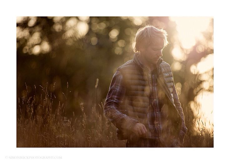 Outdoors, surf, snow sports lifestyle portrait of a blonde haired male in Rab gilet and check shirt standing in field, backlit by low winter sun.