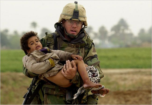 "This photo of former Pfc. Joseph Patrick Dwyer was taken on March 25, 2003 in the town of Mishkab south of Baghdad, as the soldier carried the young boy to safety."" The former Army medic died of an apparent overdose in July 2008"