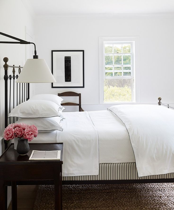 white master bedroom. white bedding, black iron bed, pink flowers