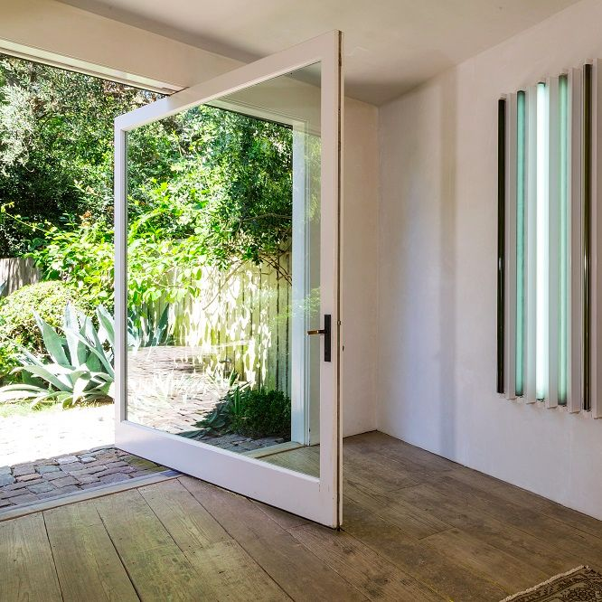 The front door and entryway to this Frank Gehry-designed modern estate in Malibu, California that's owned by actor Patrick Dempsey.