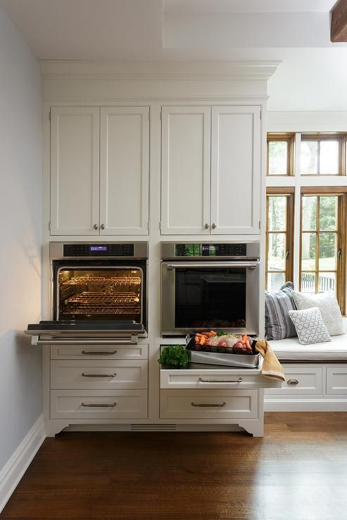 Side by side wall oven are mounted beneath white shaker cabinets and above drawers fitted with a stainless steel pull out tray countertop.