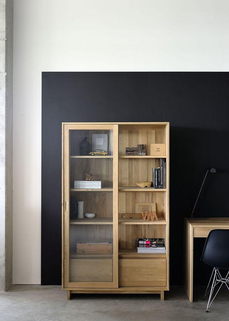 Wave bokhylla med lådor nertill, tillverkad av belgiska Ethnicraft i massivt trä. Bokhyllan har två skjutbara dörrar i glas. Wavekollektionen kännetecknas av sina subtila konturer och den framstående formen på stativet.