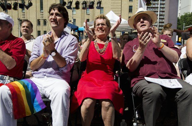 Liberal Party of Canada leader Justin Trudeau (L), Canada's first openly gay Ontario Premier Kathleen Wynne (C), and former interim leader for the Liberal Party of Canada Bob Rae attend an outdoor church service before the gay pride parade in Toronto, June 30, 2013.