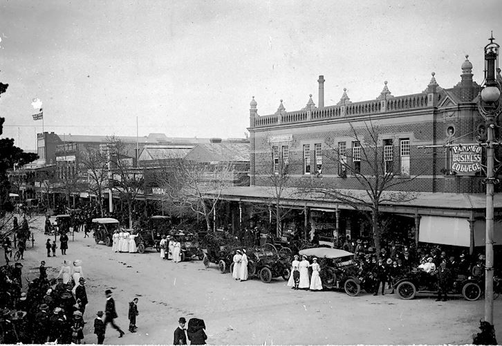 A number of decorated cars parked along the street with nurses standing beside them. There are crowds of onlookers. The occasion may have been Hospital Rose Day. The Bendigo Business College is across the street. Bendigo Business College, Bendigo, Victoria, Australia, 25 Oct 1915 W H Robinson Studio, 25 Oct 1915