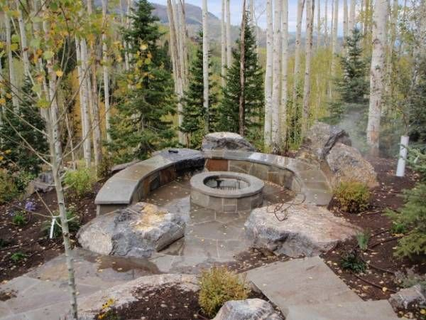 The large boulders create a more natural, rugged look for this mountainside firepit. The mortared flagstone has been built around the boulders to blend them together nicely. Picture compliments of www.american-stone.com