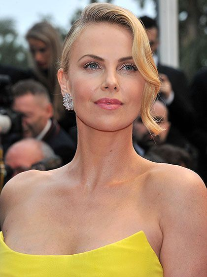 2015 Cannes Film Festival - Charlize Theron's updo with curled face-framing bangs, pearly eyeshadow and pink lips | allure.com