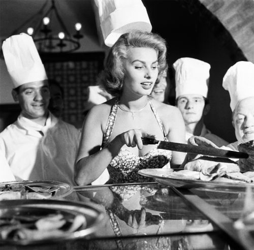Sophia Loren cutting bread with a big knife, surrounded by cooks in a restaurant kitchen, Venice