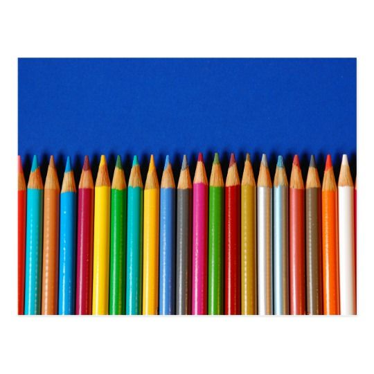 Colorful pencil crayons on blue background postcard