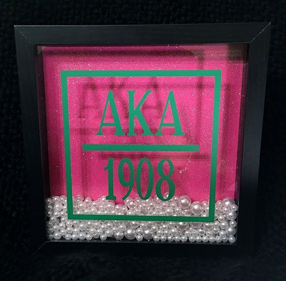 AKA themed Shadow Boxes definitely make a statement amongst Sorors!!!! This beauty will be a unique addition to your decor, great for your home or office. It's perfect for you or as a gift. Black shadow box is filled with pearl accents against a glittery pink background. The frame