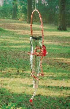 DIY Hummingbird Feeder  Forget pricey, decorative sugar-water feeders. Make this recycled DIY hummingbird feeder for just a few bucks by using a recycled bottle and inexpensive decorative accents.