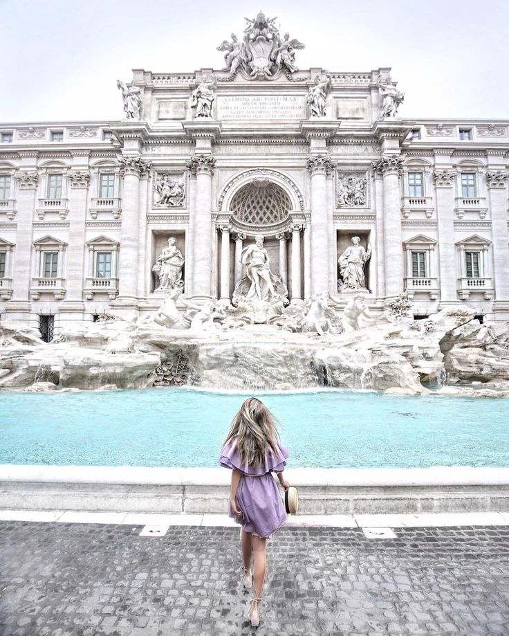 This travel shot is so pretty! We don't know where this is but it looks like someplace in Europe, which we would love to visit and explore! The purple of the dress plays so well off of the blue water and the white building!