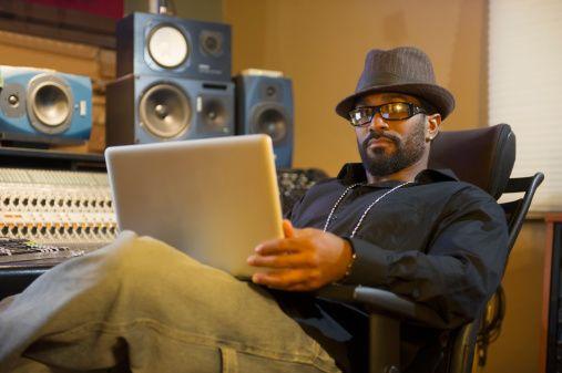 Mixed race musician recording in studio