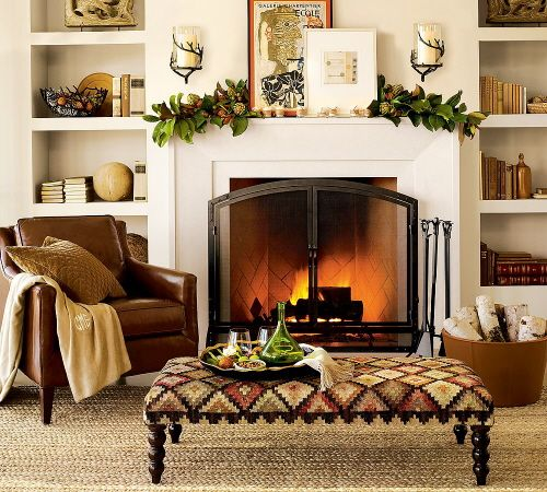Layered artwork, branch hurricane sconces, and a magnolia leaf garland complete this living room ready for the autumn chill