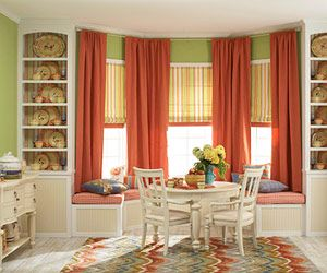 so love this bay window area..window treatments, seating, and book shelves