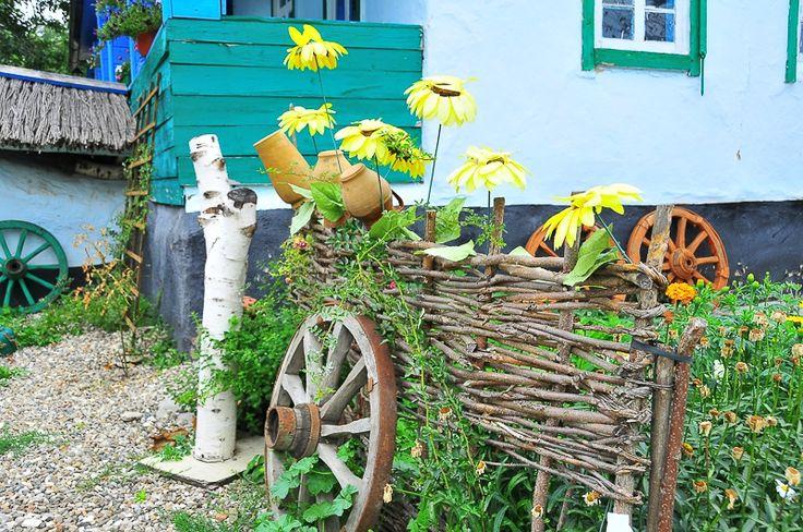 Плетеный забор в русском деревенском стиле с горшами на колышке и старым колесом от телеги