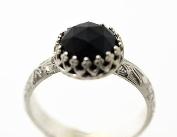 This handforged engagement ring features a 10mm rose cut black onyx gemstone set into a sterling silver crown bezel. Onyx is a form of chalcedony,