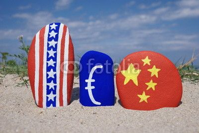 USA, Euro, China symbols on stones with sand background