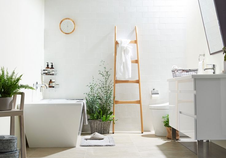 This design is a practice in simplicity. White tile walls and cream tile floors keep it clean and crisp. A leaning ladder for towels and clock add warm wood to the look.