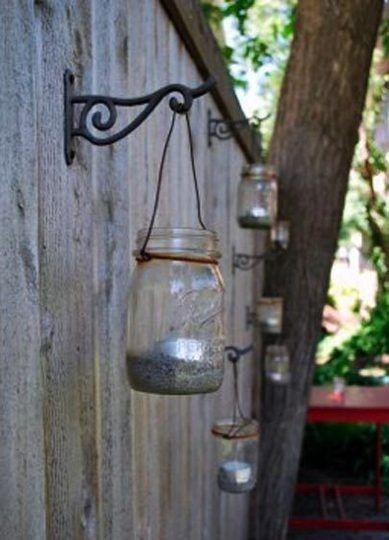 Mason jar tea lights on fence - maybe do this with the solar powered jar lights...