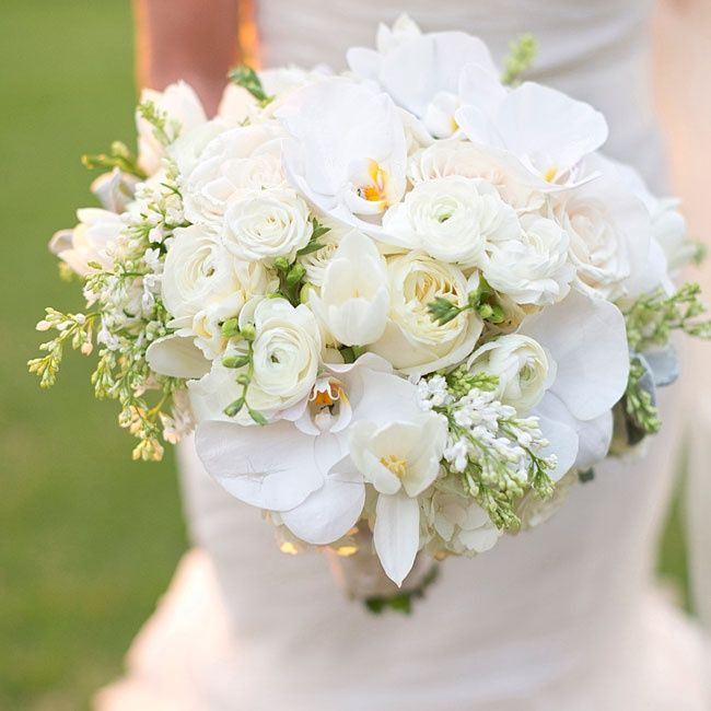 All-white bouquet of dendrobium and phaleonopsis orchids, hydrangeas, amaryllis and roses.