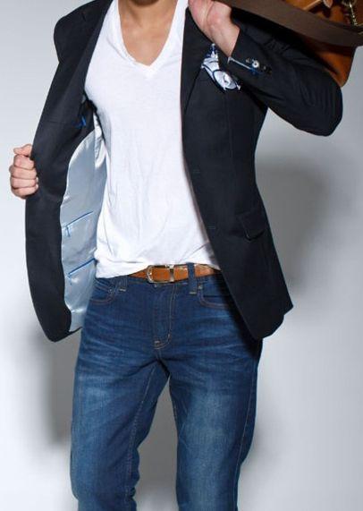 Winner. Dark smart navy blazer, tucked in white v neck t-shirt and blue denim jeans. Brown leather holdall & belt to finish.